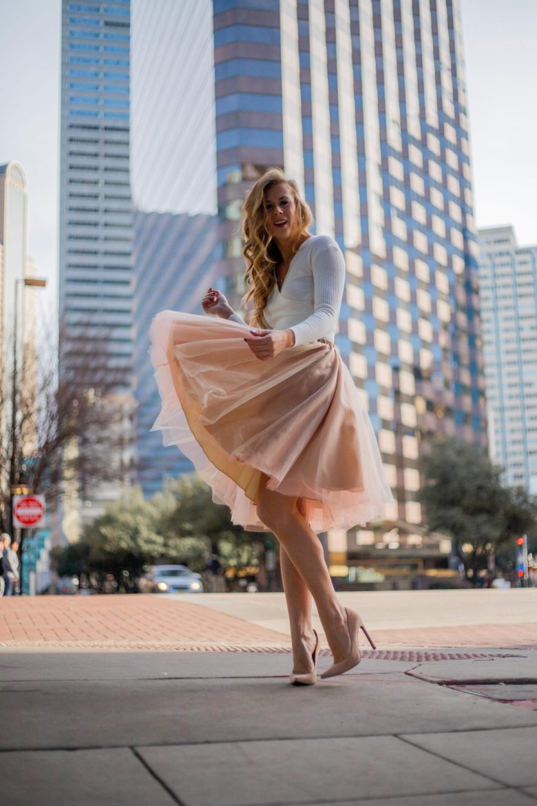 Kasey Goedeker twirling downtown in a pink tulle skirt and white wrap sweater with nude pumps