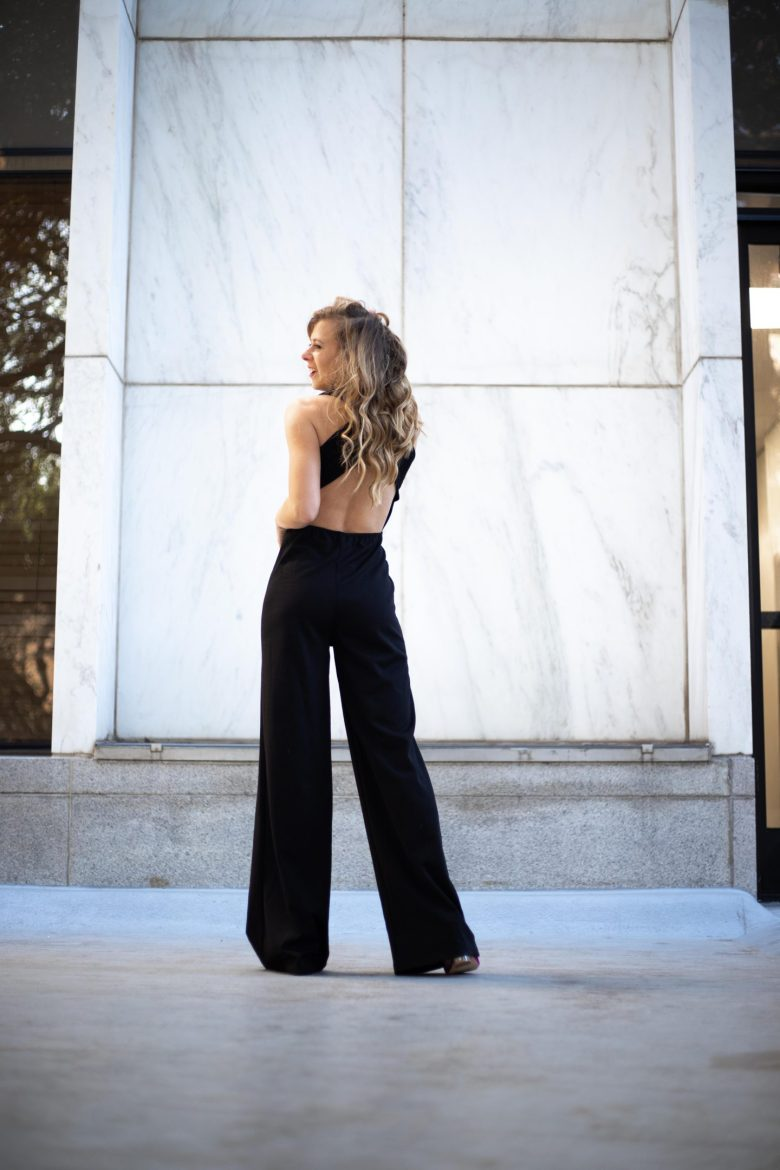 Kasey Goedeker of Running in Heels wears a black open back jumpsuit standing in front of a marble wall