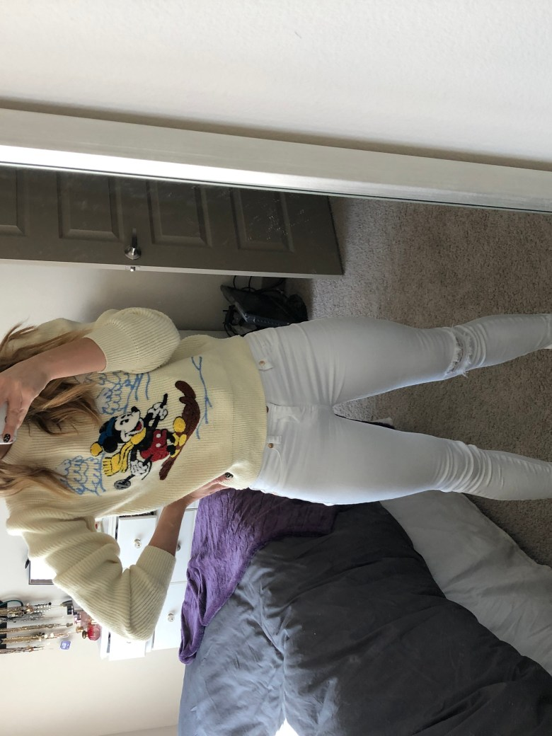 Everyday Outfit- Weekend look! Vintage Disney Christmas sweater paired with Blank NYC white jeans, lace up booties, and Christmas earrings by Sugarfix by Baublebar