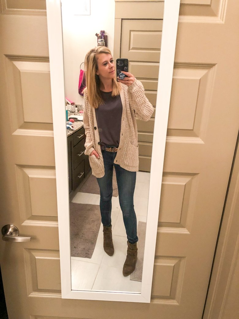 Top US fashion and lifestyle blogger wears gray t-shirt, waffle knit cardigan, snakeskin belt, and suede Italeau booties.