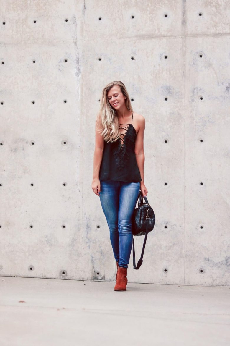Lace Up Cami Comparison featured by top US fashion blog, Running in Heels: image of a blonde woman wearing a lace-up cami by WAYF, DL1961 denim, and Italeau boots while carrying an ALexander Wang Rockie bag.