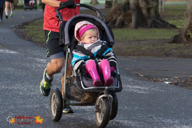Child in running buggy wearing parents' jumpers