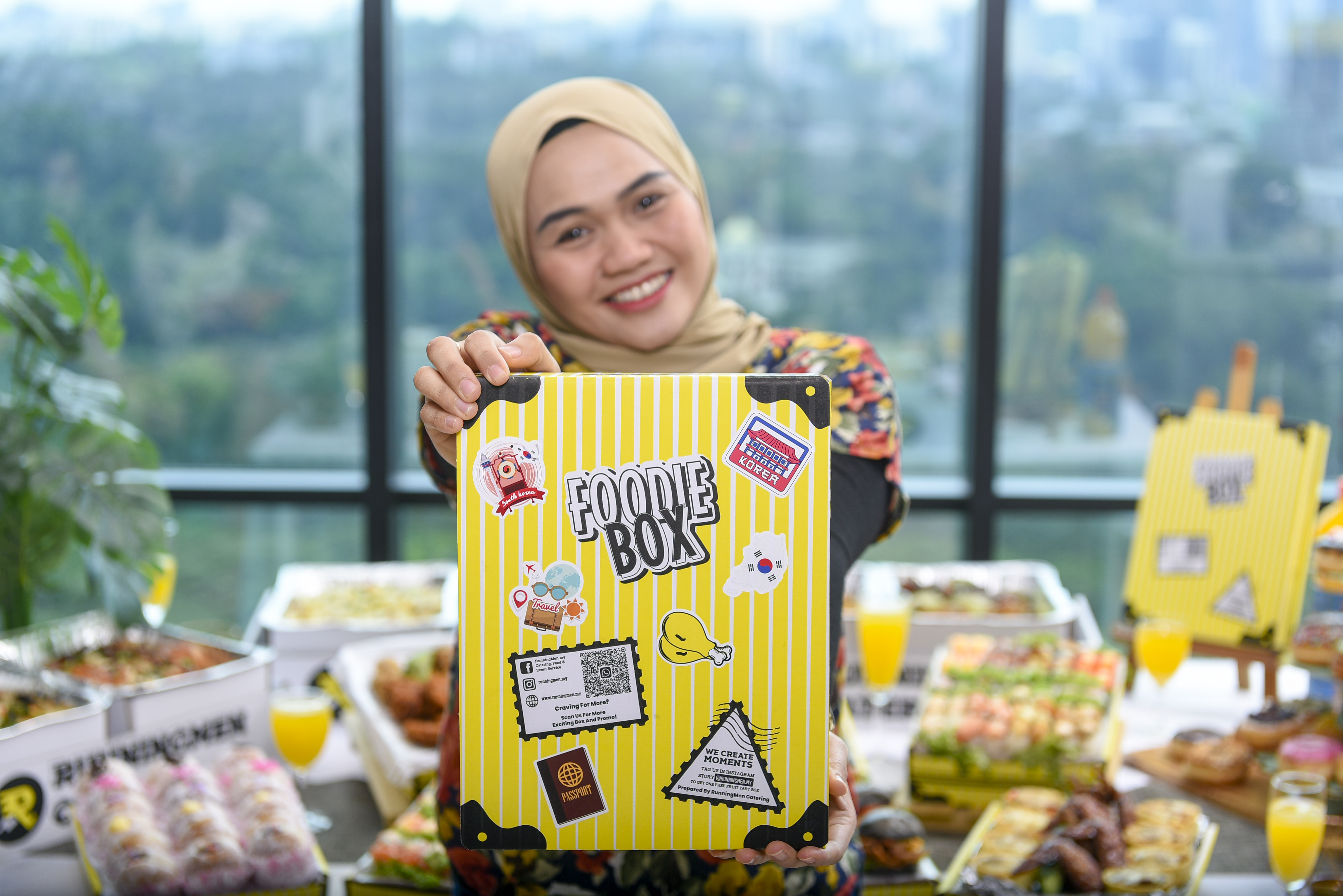 a malay girl holding runningmen catering's foodie box travel theme luggage box