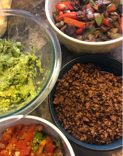 Taco night spread with guacamole, veggies, pico di gallo and ground beef
