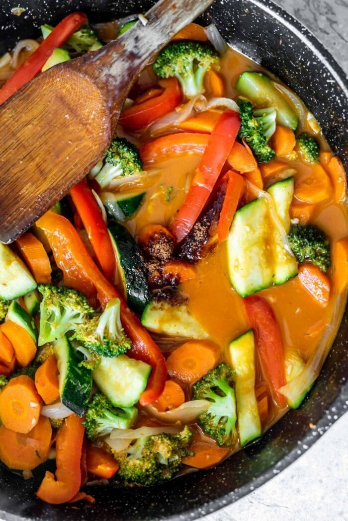 Vegetable red curry in a skillet with coconut sugar being mixed in with a wooden spoon.