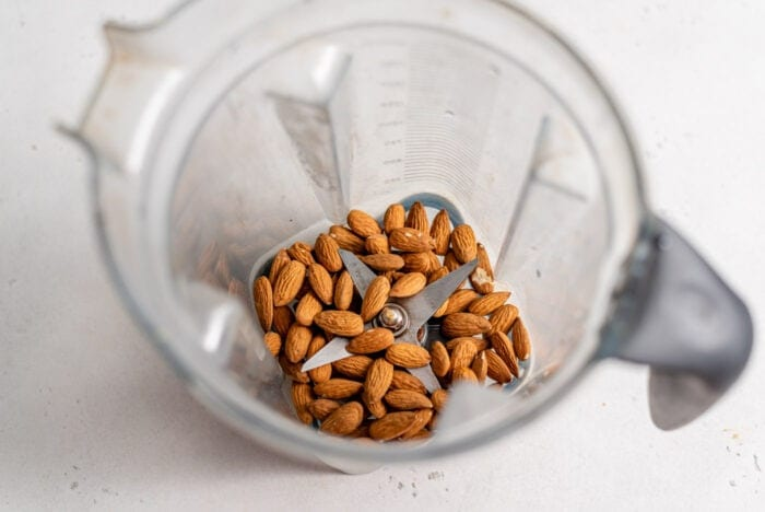 Raw almonds in a blender container.