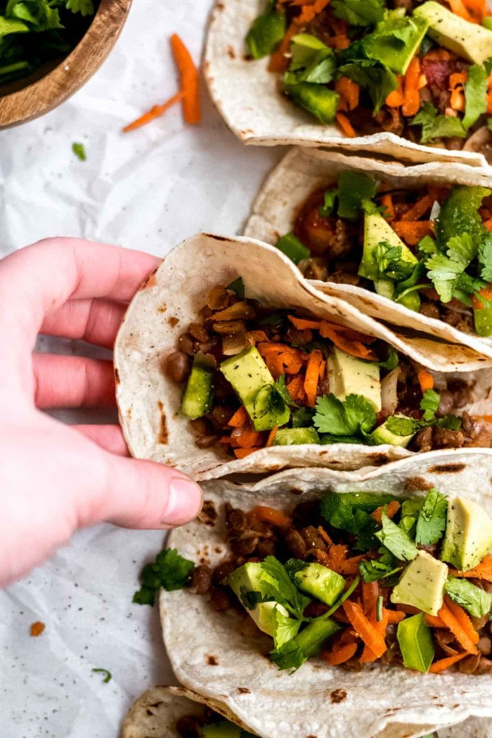 Hand picking up a vegan lentil taco with avocado, carrot and salsa.