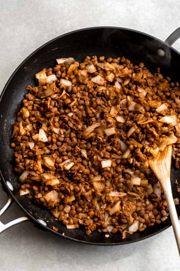 Vegan lentil taco filling in a skillet with a wood spoon.