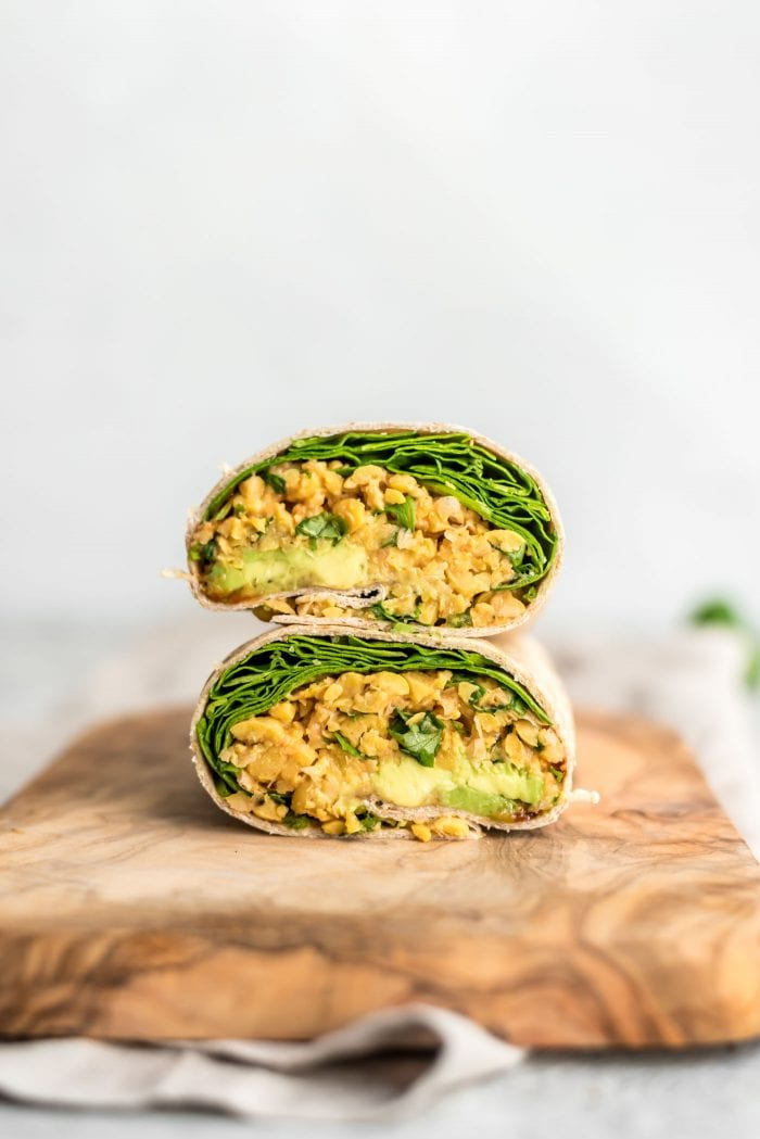 Two halves of a wrap stuffed with chickpeas and avocado.