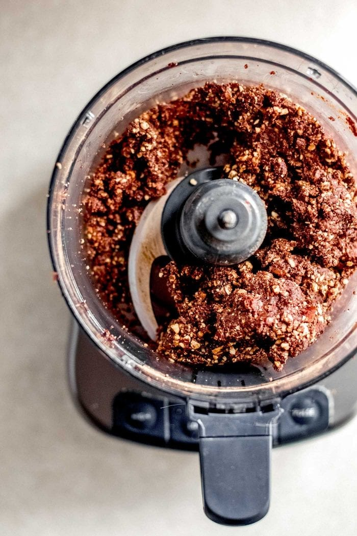 A thick, sticky chocolate dough in a food processor.
