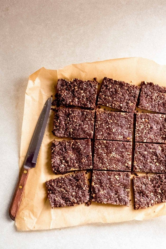 Chocolate energy bars cut into bars on a piece of parchment paper.