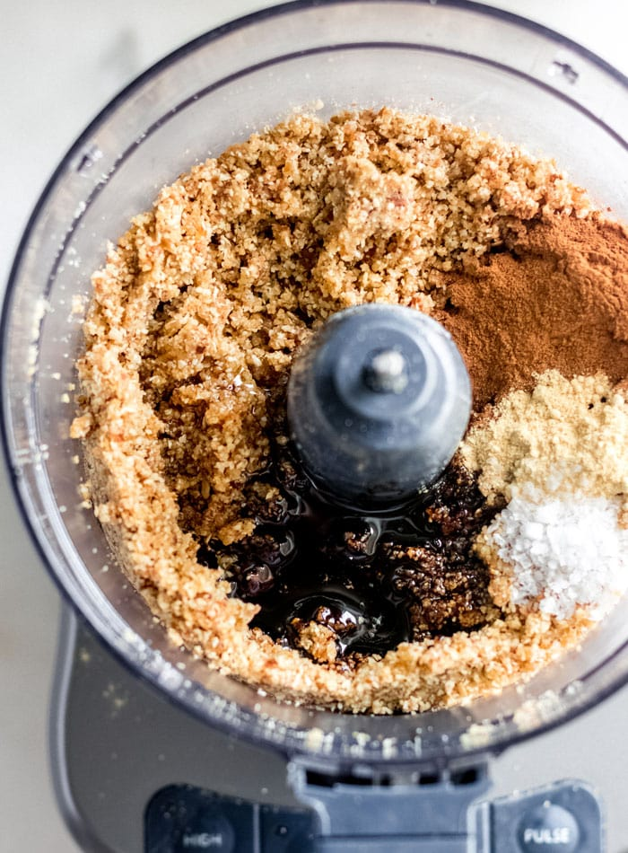 Spices, molasses and salt added to a dough mixture in a food processor.