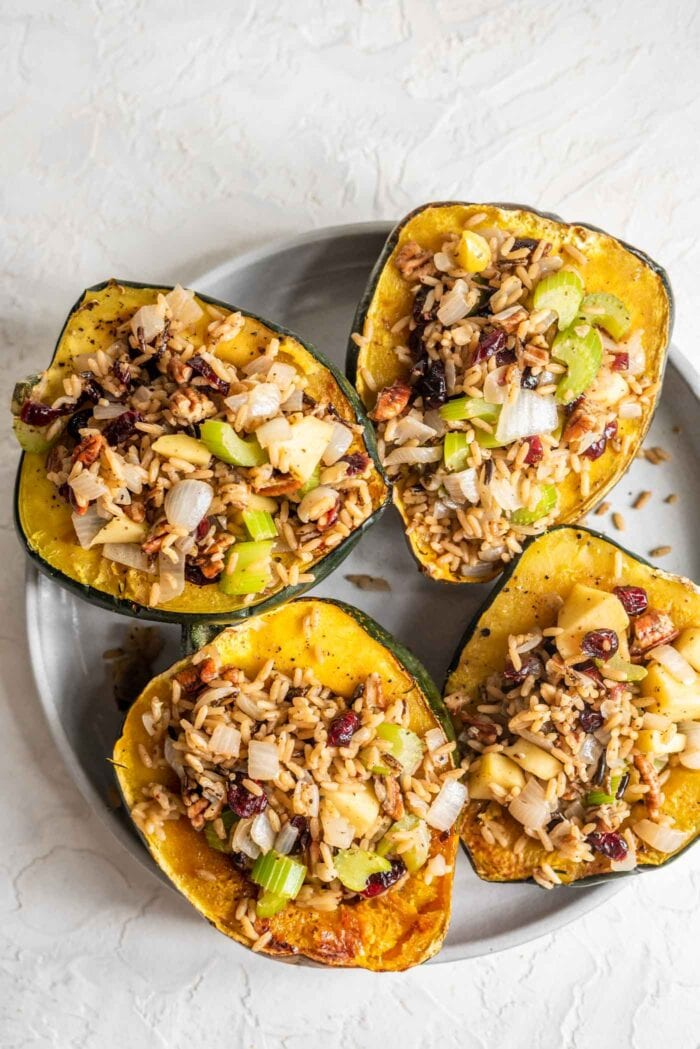4 vegan stuffed acorn squash on a grey plate.