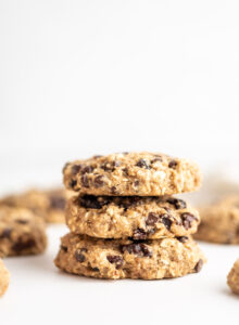 A stack of 3 vegan oatmeal raisins chocolate chips cookies against a white background.