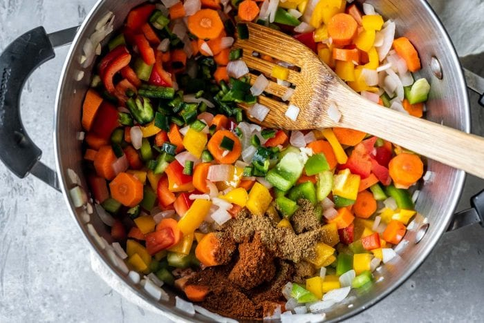 Diced bell peppers, jalapeno and spices in a soup pot with a wooden spoon.