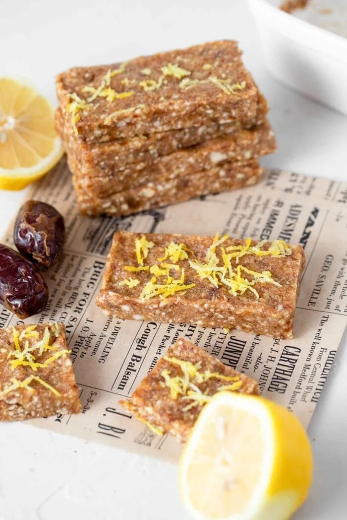 Energy bars topped with fresh lemon zest sitting on a kitchen counter.