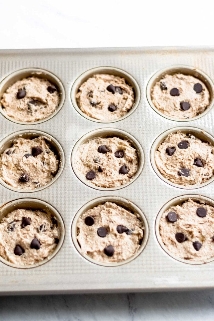 Raw muffin batter in muffin tins.