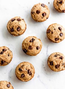 Vegan chocolate chip banana muffins on a marble surface.