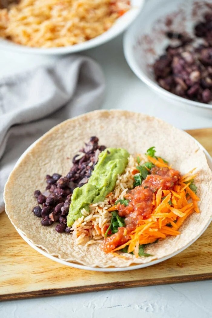 Avocado, rice, black beans and veggies in a large tortilla.
