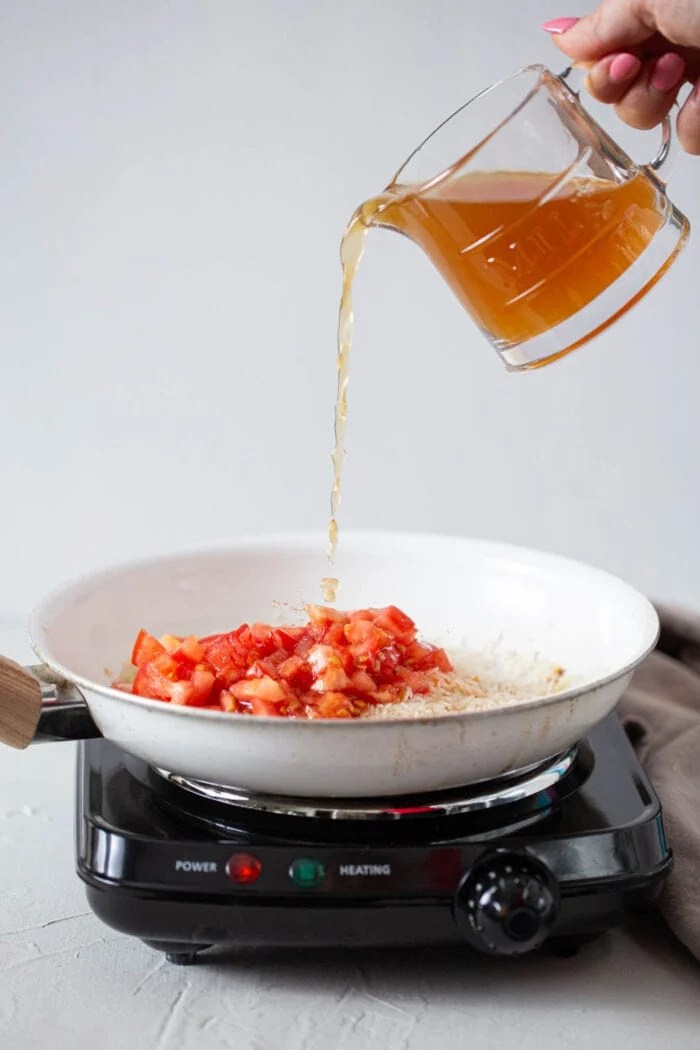 Broth being poured into a skillet of rice and tomatoes on a cooktop.