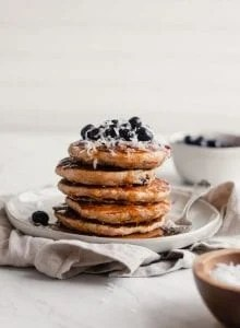 Stack of vegan blueberry coconut pancake with blueberries and coconut on top.