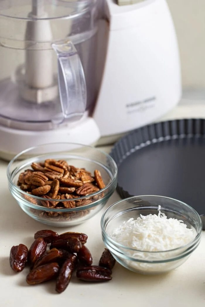 Dates, coconut and pecans in 3 small glass containers.