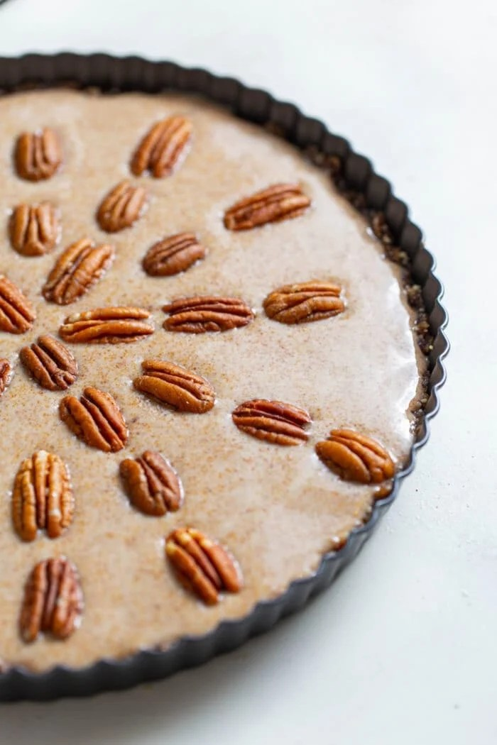 Raw vegan maple pecan pie in a pie dish topped with pecans.