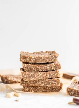 Stack of 5 vegan paleo energy bars sitting on parchment paper against a white background.