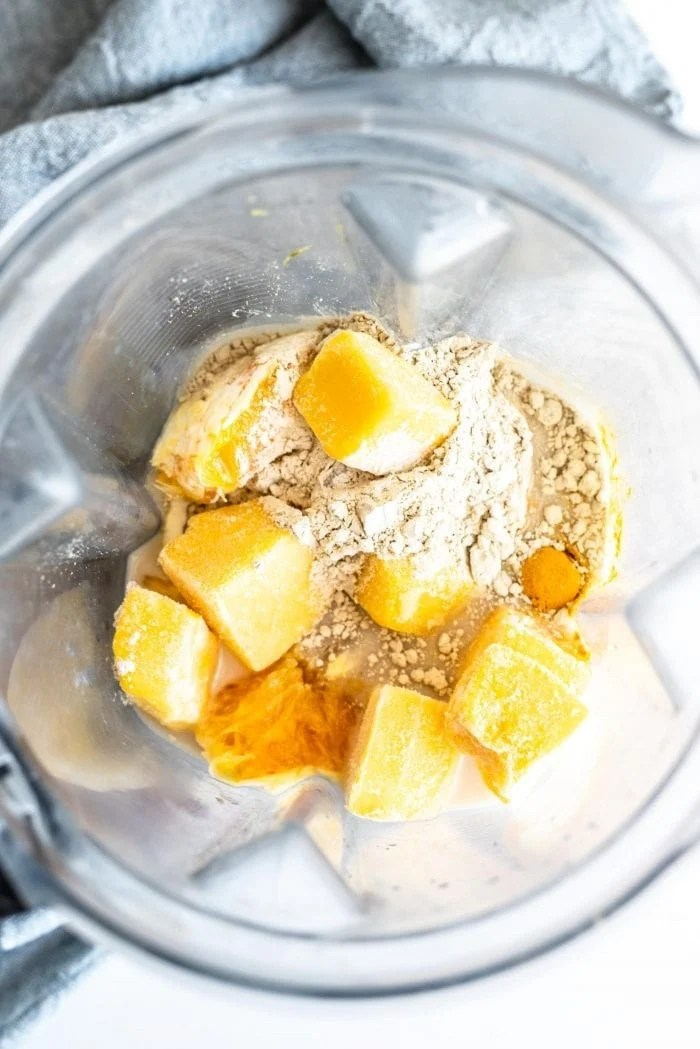 Frozen mango, orange, almond milk, protein powder, frozen banana and turmeric in a blender.