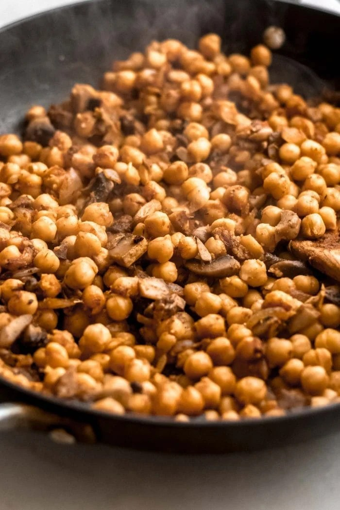 Spiced chickpeas in a skillet with a wooden spoon.