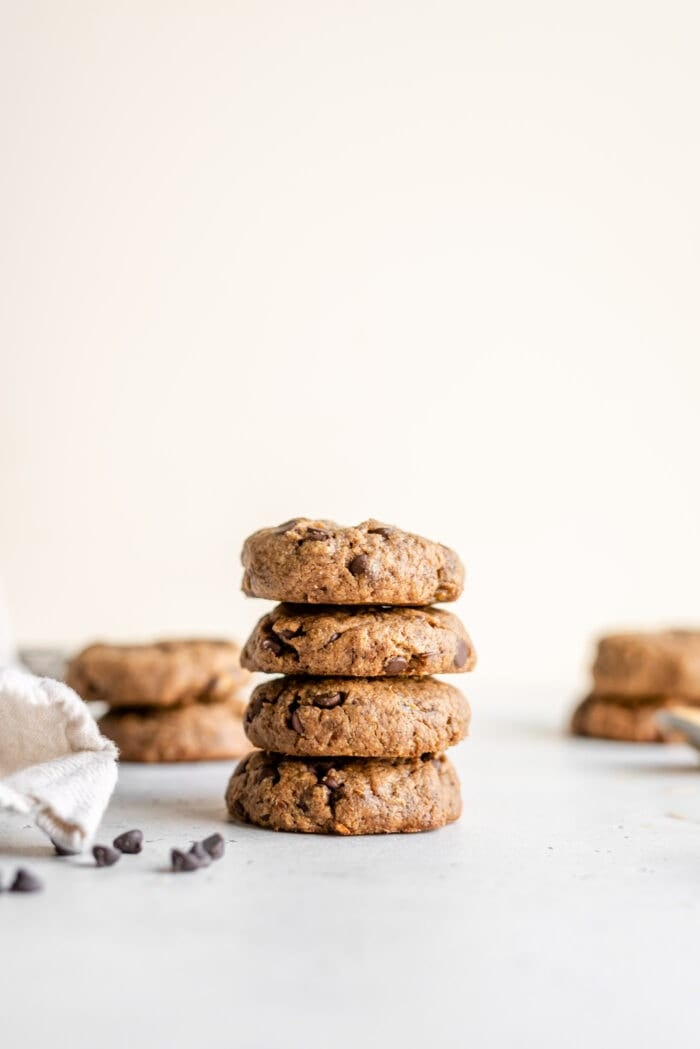 4 grain-free peanut butter cookies on a white surface with a few chocolate chips scattered around,.