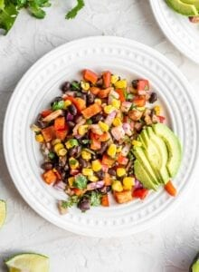 Black bean corn salad with avocado on a small white plate with cilantro and lime on the side.
