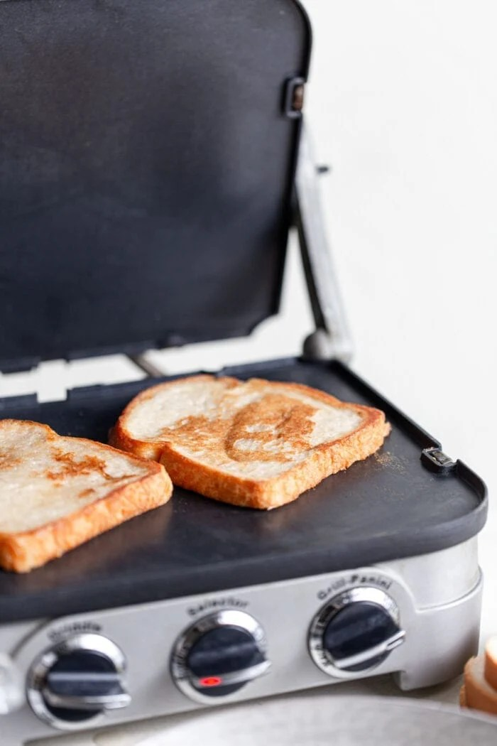 Vegan French toast being grilled on a griddle.