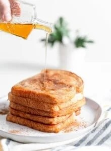 A stack of coconut vegan french toast being topped with maple syrup.
