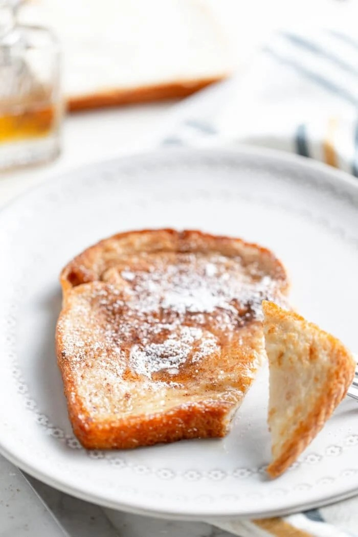A slice of vegan French toast toped with sugar and maple syrup on a white plate.