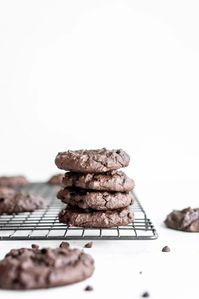 Stack of 4 chocolate vegan protein cookies sitting on a cooling rack with some chocolate chips sprinkled around them.