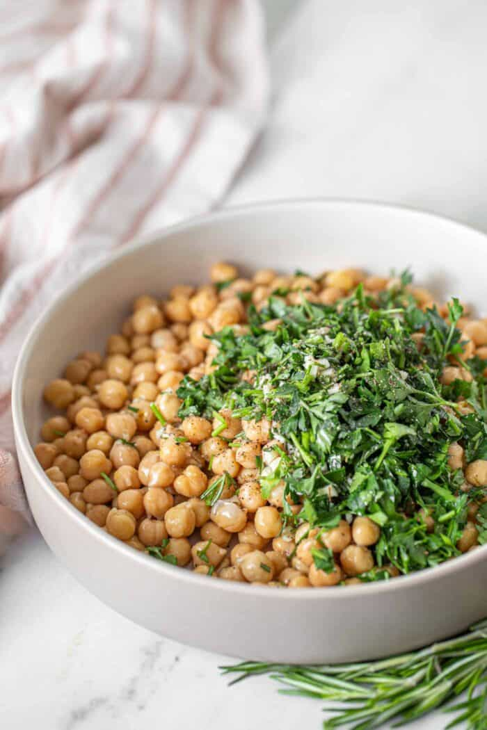 Chopped fresh rosemary and parsley in a bowl with chickpeas.