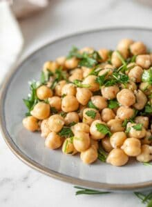A simple chickpea salad with chopped herbs and garlic on a small plate.