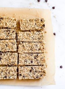 10 sliced oatmeal chocolate chip bars sitting on parchment paper. Chocolate chips scattered around.