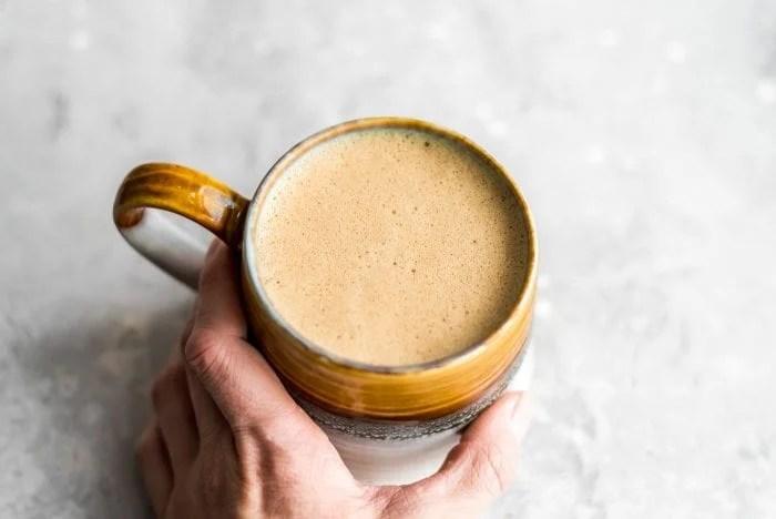 A hand grabbing a mug of vegan bulletproof coffee.