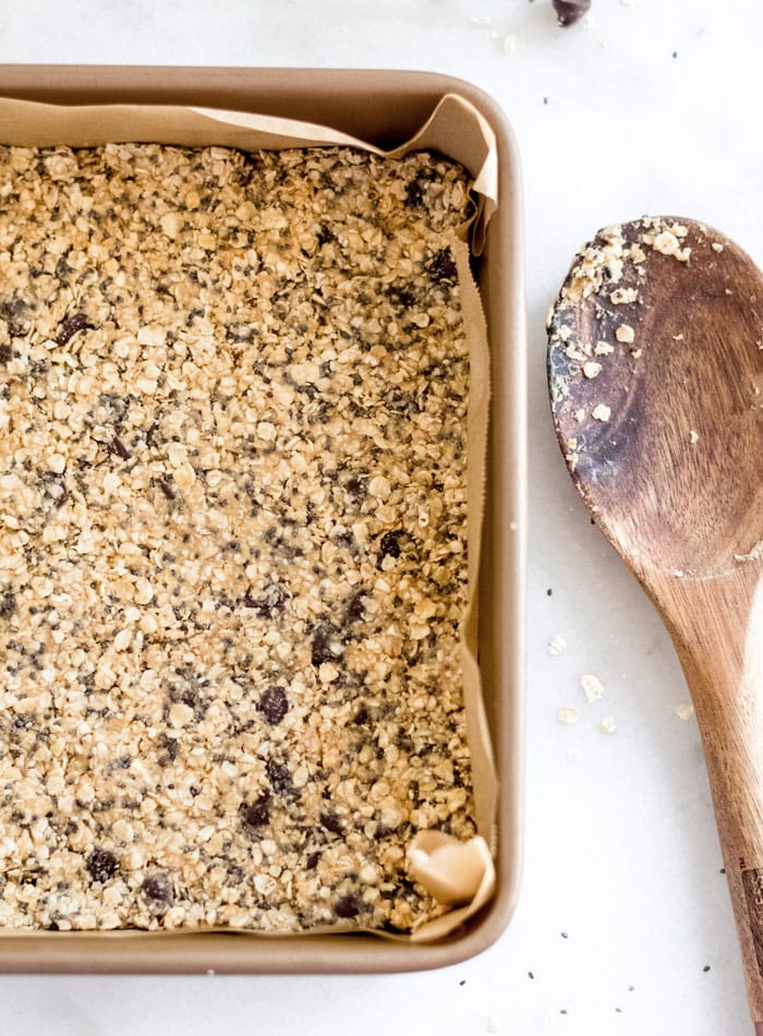 Chocolate chip oatmeal dough firmly pressed into a lined square baking pan. Wooden spoon rests beside.