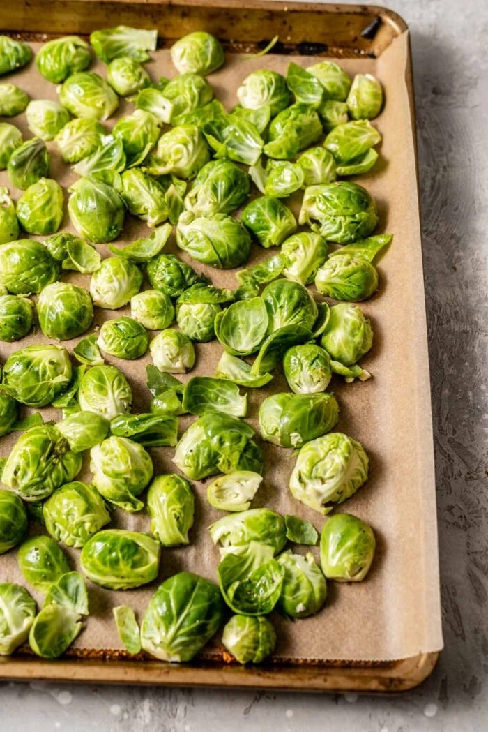 Raw chopped brussels sprouts on a baking pan lined with parchment paper.