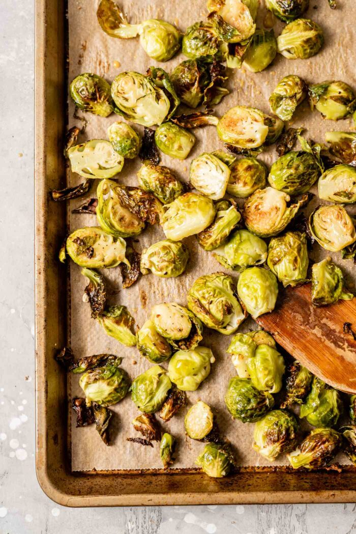 Maple dijon roasted brussel sprouts and a wooden spatula on a baking tray lined with parchment paper.