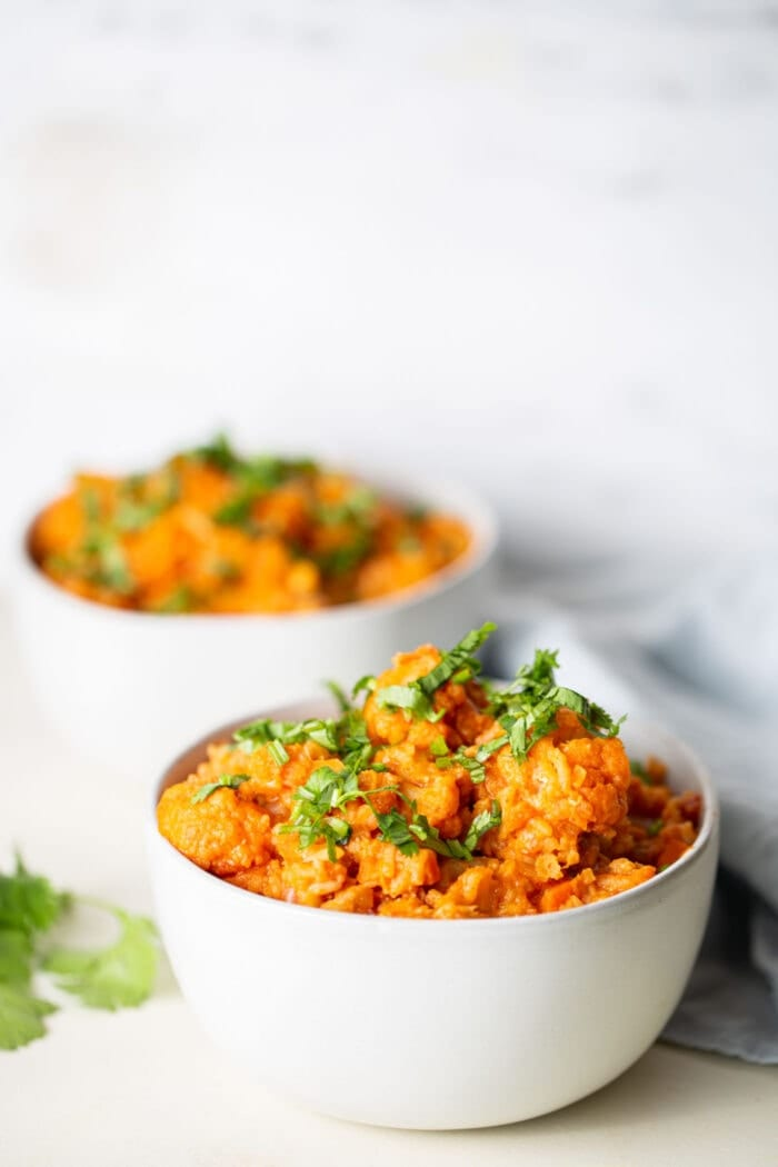 Two white bowls of vegan red lentil cauliflower curry topped with cilantro.