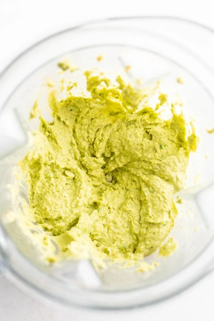 Blended avocado hummus in a Vitamix blender container.