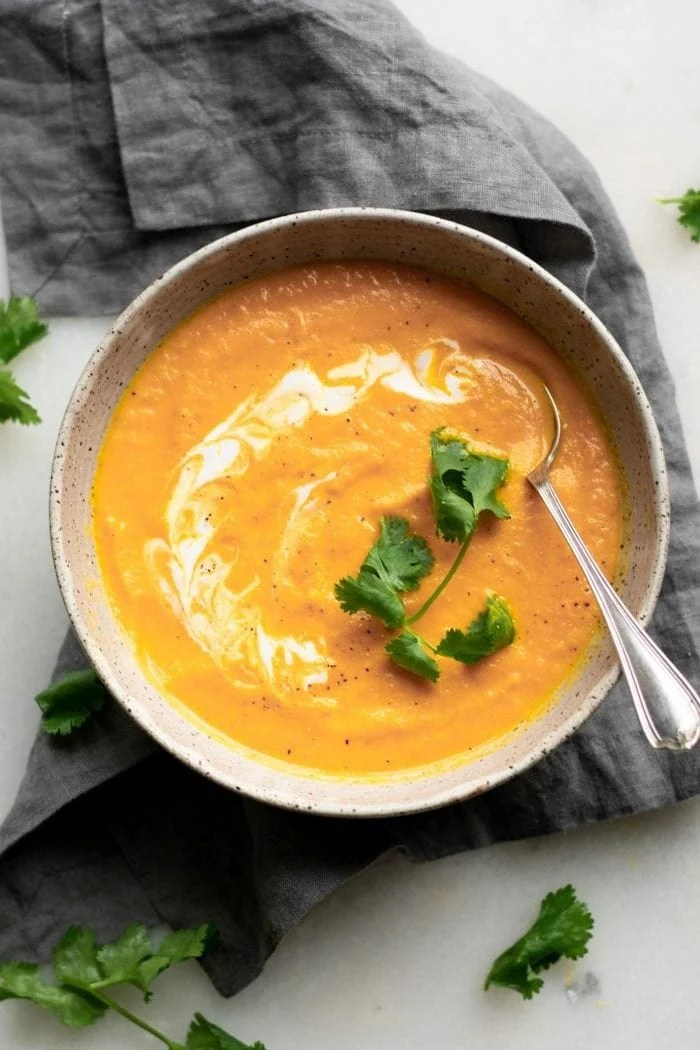 Healthy vegan coconut ginger carrot soup with cilantro and coconut milk.