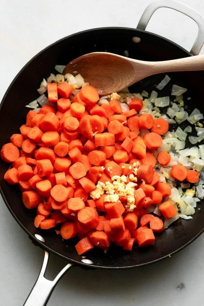 Cooking carrots, ginger, onion and garlic in a sauce pan to make coconut ginger carrot soup.