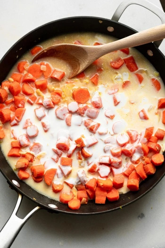 Carrots and coconut milk in a skillet with a wooden spoon.