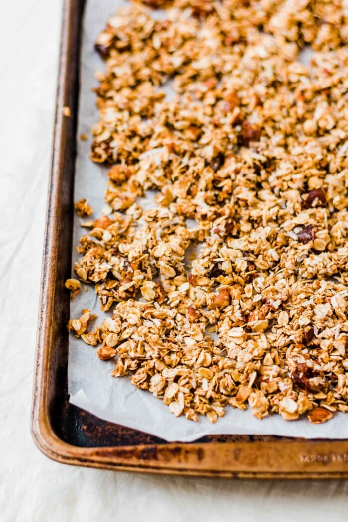 Baked pumpkin granola on a baking tray lined with parchment paper.