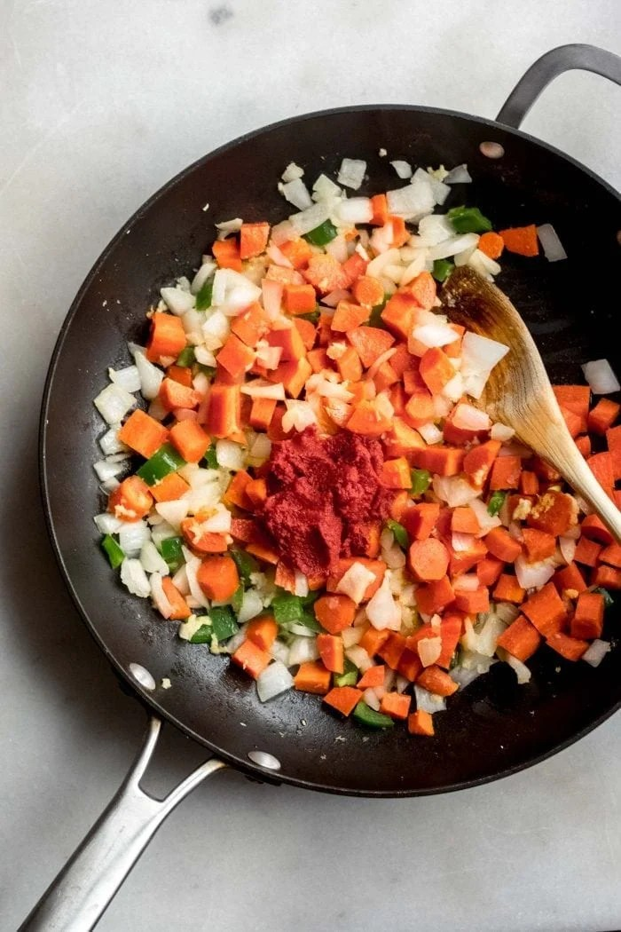 Veggies and red curry paste in a skillet for making Thai Red Curry Cauliflower Rice.